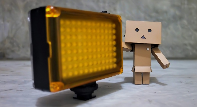 Morris Lighting Reviews an LED Panel with a Cardboard Figure Next to it