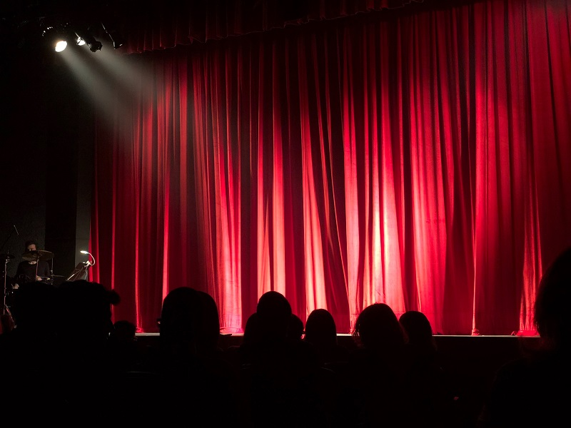 Floodlights vs Spotlights A Stage with a Red Curtain and a Spotlight Shining on it