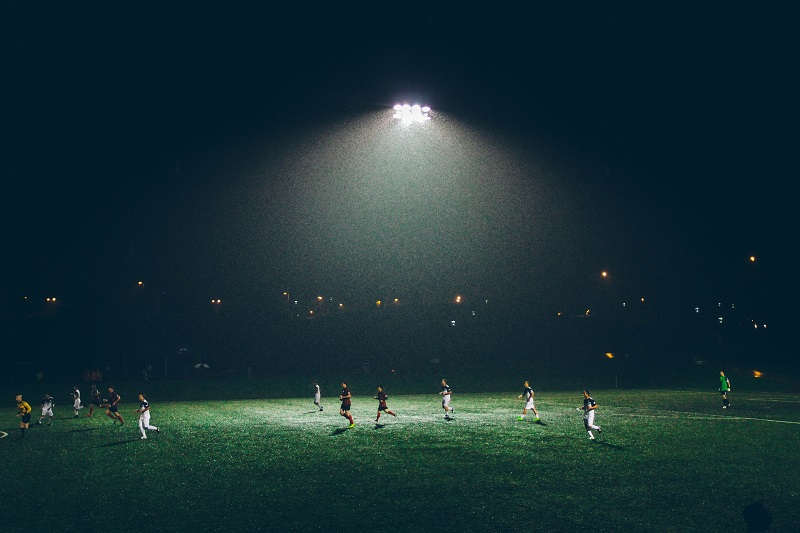 Floodlights vs Spotlights People on a Field at Night with Floodlights Shining Down on Them